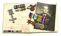 BNPS.co.uk (01202) 558833<br /> Pic: Bosleys/BNPS<br /> <br /> Pictured: The medals and log books  part of the sale.<br /> <br /> The heroics of an RAF pathfinder pilot who kept a major bombing raid on track and got his crew home with his aircraft on fire can be revealed after his medals sold for £4,300.<br /> <br /> Squadron Leader Alfred Clarke's Lancaster plane came under attack by a German night-fighter near to Cologne, setting one of its engines ablaze.<br /> <br /> The crew's rear gunner was also badly wounded and unable to defend them from a hostile barrage.<br /> <br /> Nevertheless, Sq Ldr Clarke ploughed on as following his aircraft were 282 Allied bombers relying on his crew to drop sky markers on their targets.