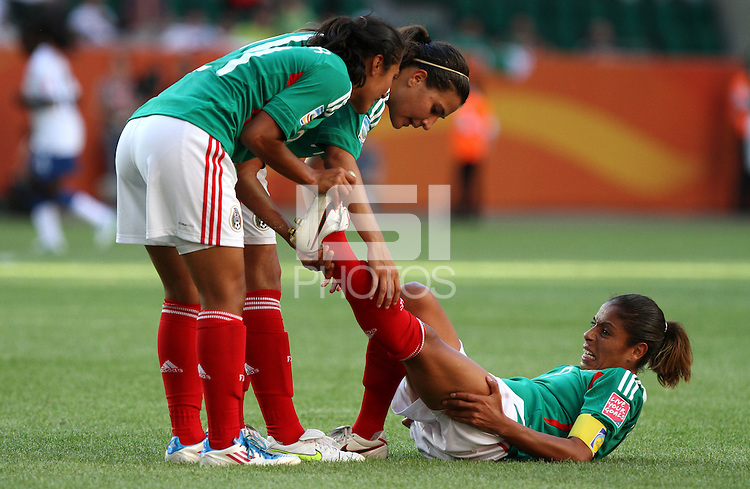 Wolfsburg , 270611 , FIFA / Frauen Weltmeisterschaft 2011 / Womens Worldcup 2011 , Gruppe B  ,  .England - Mexico .Maribel Dominguez (Mexico) mit Krampf am Boden , zwei Mitspielerinnen helfen .Foto:Karina Hessland .