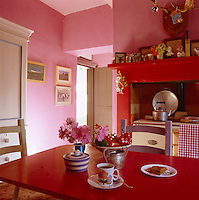 This kitchen is painted in a fresh pink with a bright red kitchen table and mantelpiece