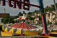 """Albania. Berat, Town center at sunset. A young girl seats and enjoys a ride on a fairground carousel. The central figure of the carousel is a woman wearing a skirt with an american flag, a hat and an open neckline revealing her generous breasts. A mosque on the left and an orthodox church on the right. Berat, historically known as Poulcheriopólis and Antipatreia, is the ninth most populous city of the Republic of Albania. The city is the capital of the surrounding Berat County. Berat, designated a UNESCO World Heritage Site in 2008, comprise a unique style of architecture with influences from several civilizations that have managed to coexist for centuries throughout the history. Berat is known to Albanians as the city of """"One above another Windows"""". The flag of the United States of America, often referred to as the American flag, is the national flag of the United States. It consists of thirteen equal horizontal stripes of red (top and bottom) alternating with white, with a blue rectangle in the canton (referred to specifically as the """"union"""") bearing fifty small, white, five-pointed stars arranged in nine offset horizontal rows, where rows of six stars (top and bottom) alternate with rows of five stars. 26.05.2018 © 2018 Didier Ruef"""