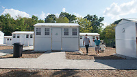 Soloman Burchfield (left), director of New Beginnings, gives a tour Tuesday Sept. 14, 2021 to Fadil Bayyari of Springdale at the microshelter project next to 7 Hills Homeless Center in south Fayetteville. The project broke ground in April 2019 and will provide 20 prefabricated homes to people experiencing chronic homelessness as well as a service building providing for basic needs. The community will operate under a resident-led code of conduct and have a staff person on site 24 hours a day. Residents are planned to start moving in next week. Visit nwaonline.com/210000915Daily/  (NWA Democrat-Gazette/J.T. Wampler)