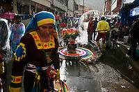 People wearing costumes walk along a street in the rain at the Carnaval de Oruro. During the fiesta many people sacrifice llamas and give offerings such as coca leaves and cigarettes to show their dedication to the Devil, a Virgin, Pachamama or Mother Earth. The Devil (or Uncle) is a mythical character that protects the miners of Oruro who work in dangerous conditions hundreds of metres below the ground. During the carnival, people dress in outrageous costumes and dance for days before arriving at the Church of Socavon, where they pay their respects to a virgin. Ironically, many of the dancers wear devil costumes.