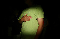 CHINA. Beijing. A Chinese man places his hand over his heart during the singing of the national anthem whilst watching the opening ceremony of the Beijing Summer Olympics. 2008