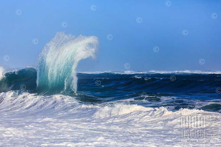 Waves converge and form a vertical wall that  leaps into the sky at Lumaha'i Beach, Kaua'i.