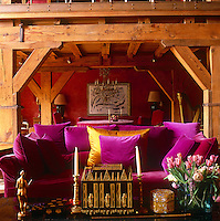 A country sitting room with a beamed ceiling and supports. Gilded ornaments and flowers are arranged on a coffee table which stands in front of a sofa upholstered in magenta pink fabric with co-ordinating cushions.