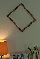 Tilted empty frame on a white wall.