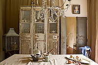 A distressed wooden display cabinet and a linen covered table furnishes a utility room off the kitchen