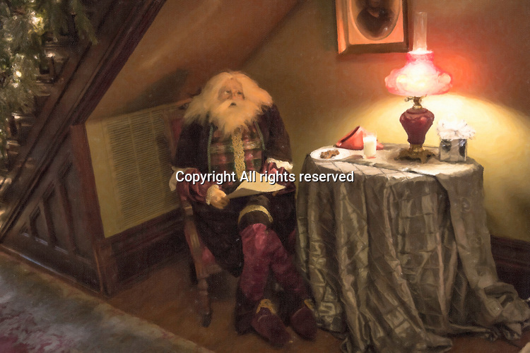 Santa sits by a table cheking his Christmas list.  Cookies and milk are on the table.