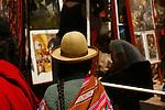 A Peruvian woman walks amongst the stalls in the Pisac market.