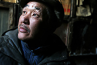 """MONGOLIA. Ulaan Baatar. """"We have been living on the streets for 10 years and in this garage for 1 year"""", said Battur,55, the grandfather of the family who, in his youth, studied Mongolian Language and Literature at one of the capital's Universities. Divorcing from his wife in the 1990's turned him to drink and hence onto the street. As the global financial crisis grips Asia, Mongolia is feeling the implications first hand as the country suffers from rising inflation pushing the price of food and fuel ever upwards. For the country's homeless, who live in sewers and abandoned garages in the capital and already face extreme discrimination and are denied access to basic health and social care, their lives are hanging in the balance. 2008"""