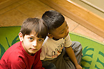 Education preschoool children ages 3-5 two boys sitting on floor one looking at camera portrait serious expression horizontal