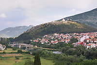 An old Roman stone bridge across the river Trebisnjica. Houses. The monastery Gracanica on the historic hill known as Crkvina against a mountain backdrop. Trebinje. Republika Srpska. Bosnia Herzegovina, Europe.
