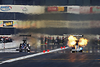 Feb. 17, 2013; Pomona, CA, USA; NHRA top fuel dragster driver Antron Brown f(right) explodes an engine during first round of alongside Larry Dixon at the Winternationals at Auto Club Raceway at Pomona. Mandatory Credit: Mark J. Rebilas-
