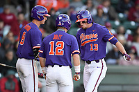 Left fielder Drew Wharton (13) of the Clemson Tigers shouts as he celebrates with teammated Logan Davidson and Robert Jolly after scoring the Tigers' fifth run in the Reedy River Rivalry game against the South Carolina Gamecocks on Saturday, March 3, 2018, at Fluor Field at the West End in Greenville, South Carolina. Clemson won, 5-1. (Tom Priddy/Four Seam Images)