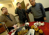Men toast with tiger wine at a restaurant in Guilin, Guangxi Province, China. The wine is made by the Xiongsen Liquor Limited Company which uses tiger bones to make tiger wine used to treat arthritis amongst other things.