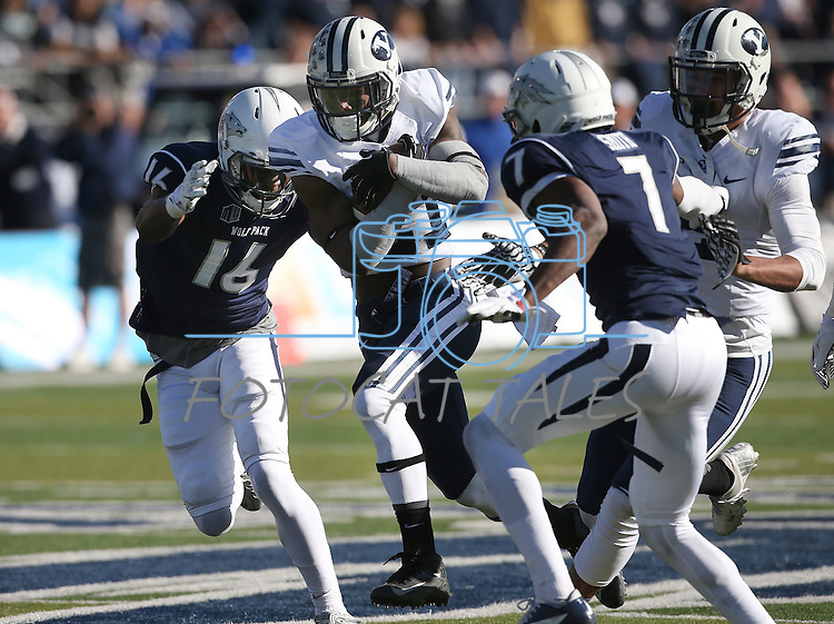 BYU's Jamaal Williams (21) tries to run through Nevada's Kaodi Dike (16) and Markus Smith (7) during the first half of an NCAA college football game in Reno, Nev., on Saturday, Nov. 30, 2013. (AP Photo/Cathleen Allison)