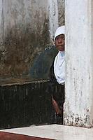 Zanzibar, Tanzania.  Girl Waiting for the Rain to Stop.  Stone Town.
