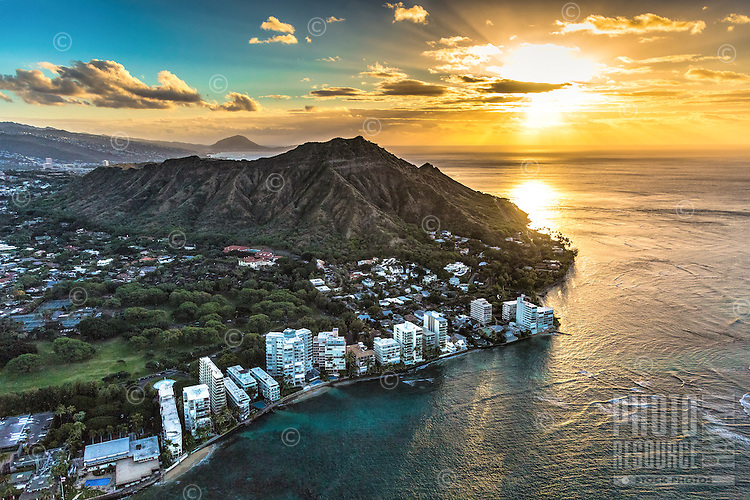 """An aerial view of the rising sun's light reflecting on the ocean along the """"gold coast"""" of O'ahu, with Diamond Head at the center."""