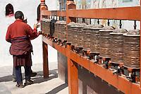 Bodhnath, Nepal.  Buddhist Worshiper Turning Prayer Wheels.