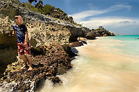 A young boy relaxes on a rock formation in the sandy beach and aqua water below the pre-Columbian Maya city, Tulum, near Cancun, Mexico.