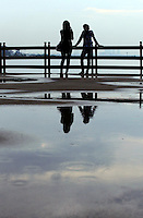 A young couple takes photographs of each other at sunset in Jakarta's port area.<br /> <br /> To license this image, please contact the National Geographic Creative Collection:<br /> <br /> Image ID: 1574996 <br />  <br /> Email: natgeocreative@ngs.org<br /> <br /> Telephone: 202 857 7537 / Toll Free 800 434 2244<br /> <br /> National Geographic Creative<br /> 1145 17th St NW, Washington DC 20036