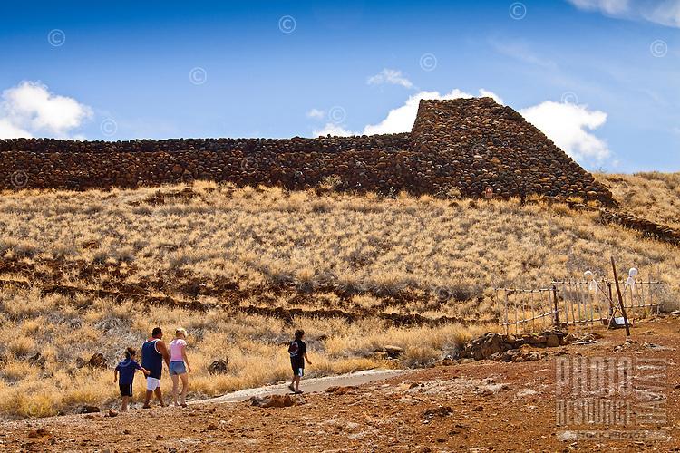A family walking towards Pu'ukohola Heiau (a.k.a. the temple on the whale hill), the largest and last heiau constructed in 1790-91 by Kamehameha I, Pu'ukohola Heiau National Historic Site, Kawaihae, Kohala, Big Island.