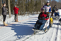 Katherine Keith and team run past spectators on the bike/ski trail during the Anchorage ceremonial start during the 2014 Iditarod race.<br /> Photo by Britt Coon/IditarodPhotos.com