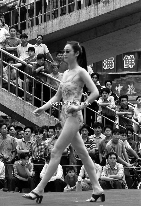 """Men gather around a """"fashion show"""" in Shenzhen, south China. China's One Child Policy coupled with the nation-wide desire for sons has resulted in a massive gender inbalance in China.   Men are beginning to have trouble finding brides in areas and the black-market trade in women and girls is getting worse.<br /> Apr 2000<br /> <br /> photo by Richard Jones / Sinopix"""