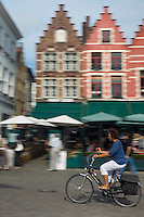 Europe/Belgique/Flandre/Flandre Occidentale/Bruges: Centre historique classé Patrimoine Mondial de l'UNESCO, Cycliste sur la Grand Place devant les terrasses des restaurants et maison à pignons à échelons  //  Belgium, Western Flanders, Bruges, historical centre listed as World Heritage by UNESCO, cyclist  on the Grand Place in front of the restaurant terraces and stepped gabled house