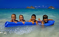 Kids playing on a blue beach raft at gorgeous Lanikai Beach on the windward side of Oahu.