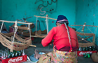 Nepal. Nepali weaving woman, posing and weaving threads for carpets. Nayapati, Eastern Kathmandu.  43