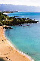 Waimea Bay, famous North Shore beach where people often jump off the large black rock near the shoreline.