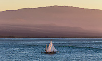 Canoe sailors hoist up their sail along the Big Island's Kohala Coast, with Hualalai Volcano looming in the distance.