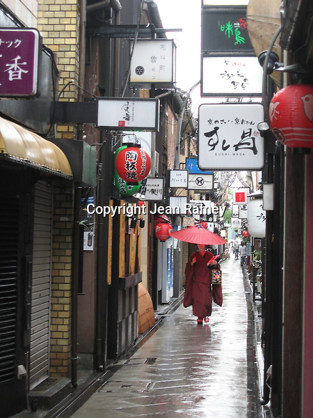 A Geisha walks through the rain under a red umbrella