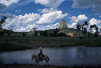 Cowboy rides along a river under Devils Tower, an ancient volcano plug  or monolithic igneous intrusion that is more than 1200 feet high. It was featured in the Hollywood movie Closer Encounters of the Third Kind in 1977.