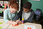 Education Elementary school grade 2 boy and girl working together on math activity