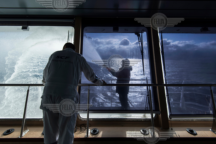 Deck crew cleaning the 'Fedor Ushakov', a multifunctional ice-breaking vessel designed to provide the year-round delivery of supplies to offshore oil platforms operating in waters off Sakhalin, and standby assistance for emergency cases. The vessel is able to hold 150 passengers, sufficient in the case of a platform evacuation.