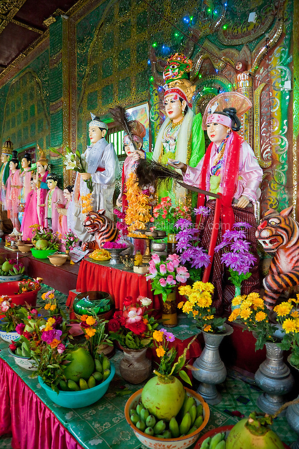 Myanmar, Burma.  Statues Representing Local Nats (Spirits) in a Shrine, Mount Popa Monastery.  Coconuts, bananas, flowers, and money have been left as offerings.