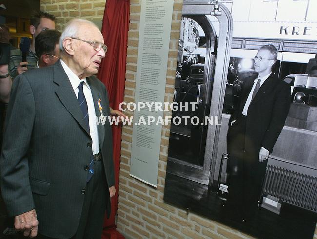 duiven 030501 de 102 jarige, zojuist als oudste nederlander geridderde  p.j.de booijs kijkt naar een foto van zichzelf (50 jaar jonger0 op de tentoonstelling van zijn werk in het duivense gemeentehuis.<br />foto frans ypma APA-foto
