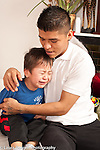 sad, crying 3 year old boy comforted by father