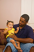 MR / Schenectady, NY. Father (22, African American) looks at his infant daughter (girl, 10 months, African American & Caucasian). MR: Dal7, Dal4. ID: AL-HD. © Ellen B. Senisi