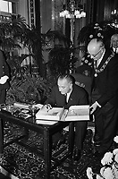 Lyndon B. Johnson in Rotterdam. The US president puts his signature in the guestbook on the right of Mayor G. E. van Walsum,  November 5, 1963<br /> <br /> <br /> Photographer Walta, Winfried / Anefo
