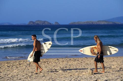 Buzios, Brazil. Surfers on the beach carrying their Malibu surfboards. Rio de Janeiro State.