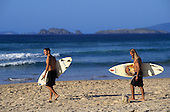 Buzios, Brazil. Surfers on the beach carrying their Malibu surfboards. Rio de Janeiro State.