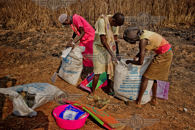 A group of South Sudanese refugees check their NFI (non-food items) sacks given to them upon their arrival at the Nyumanzi settlement.  The NFI distribution at the Nyumanzi settlement still has many challenges including poor quality and incomplete kit.