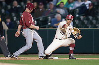 Alabama Crimson Tide outfielder Ben Moore (7) steps back to first base as Arkansas Razorbacks infielder Eric Fisher (29) reaches for the throw at Baum Stadium during the NCAA baseball game against the on March 21, 2014 in Fayetteville, Arkansas.  The Alabama Crimson Tide defeated the Arkansas Razorbacks 17-9.  (William Purnell/Four Seam Images)
