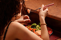 A young woman  eats  salmon ,  brocoli and vegetables.<br /> (Model Released Photo)<br /> <br /> photo (c) Pierre Roussel -  Images Distribution