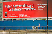 A Westminster street cleaner passes an advertising hoarding for a Virgin credit card