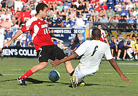 Darlington Naqbe #6 of the University of Akron slips the ball through the legs of Nick DeLeon #14 of the University of Louisville during the 2010 College Cup final at Harder Stadium, on December 12 2010, in Santa Barbara, California. Akron champions, 1-0.