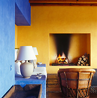 The loggia leading to the pool terrace has a built-in sofa and a floor of terracotta tiles outlined with round pebbles, the bold colours of the walls rendering decoration unnecessary